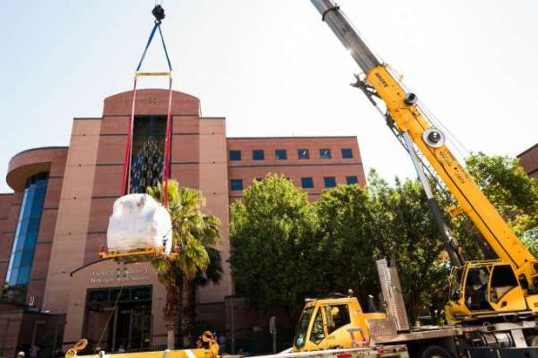 crane lifting M-R-I scanner into building