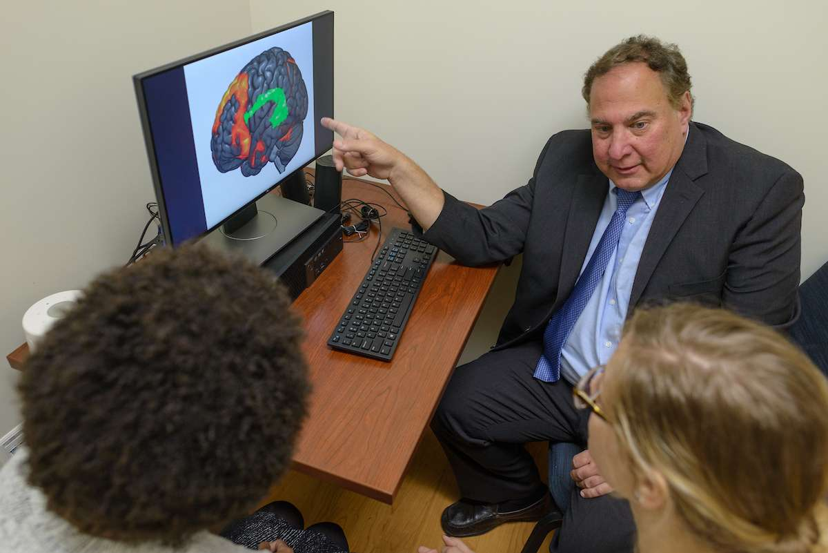 Dr. cohen pointing to a computer graphic of a brain
