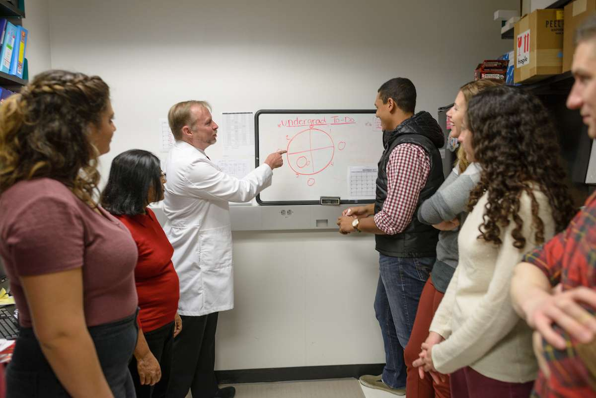 Dr. Tom Foster pointing to research poster surrounded by students